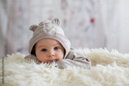 Obraz Sweet baby boy in bear overall, sleeping in bed with teddy bear - fototapety do salonu