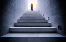 Businessman Standing On Top Of Concrete Stairs With Sun Light