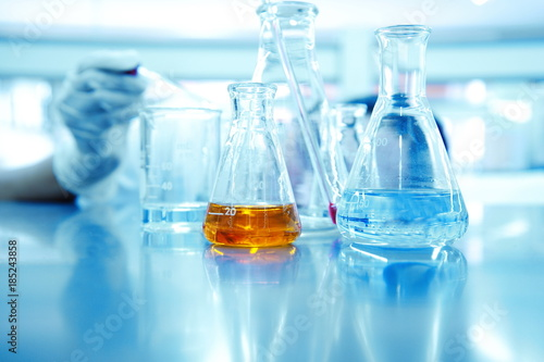 hand of scientist or reseracher drop solution in glass beaker and orange liquid in  flask at chemical science laboratory background