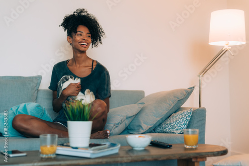 Happy young black woman sitting in the sofa giving affection to a bunny ..