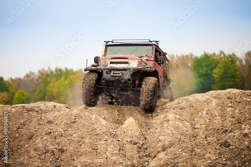 Fototapeta Classic off road car moving on dirt terrain