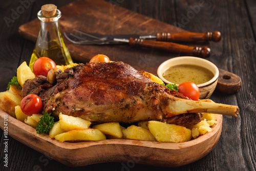 Fotomural Slow baked lamb leg with potatoes and sauce.