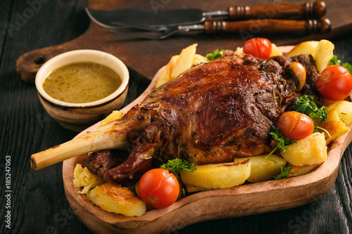 Slow baked lamb leg with potatoes and sauce.
