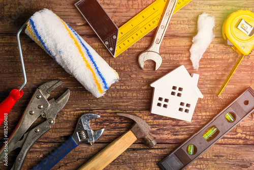 Obraz na płótnie Wooden white house toy and construction tools on wooden background with copy space