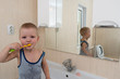 Happy boy taking bath in kitchen sink. Child playing with foam and soap bubbles in sunny bathroom with window.