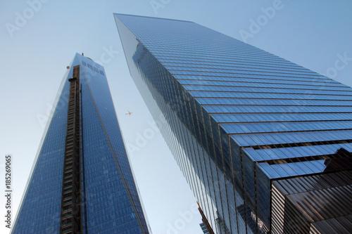 Fotografering  One World Trade Center micht daneben stehendem Hochhaus von unten mit Flugzeug