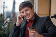 Waist up portrait of young man resting with hot drink while looking at camera. He is speaking by smartphone