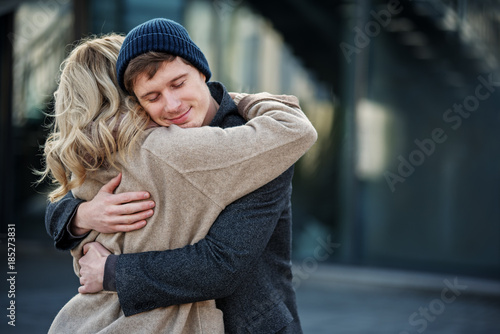 Portrait of young couple hugging each other while standing in the street Poster Mural XXL