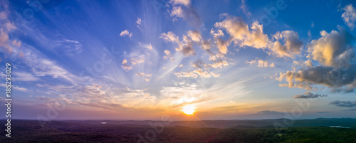 Panoramic sunset with light, puffy clouds in the sky overlooking summer New England forests Wallpaper Mural