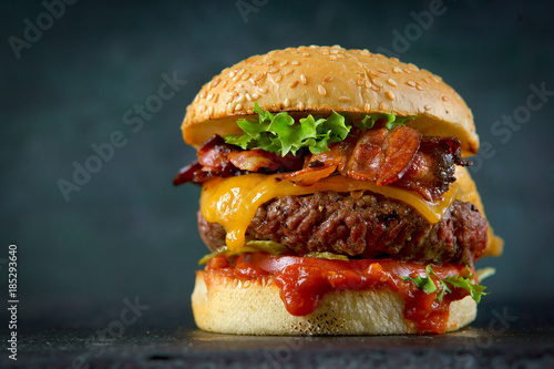 Valokuva Burger with cheese and bacon on a dark background