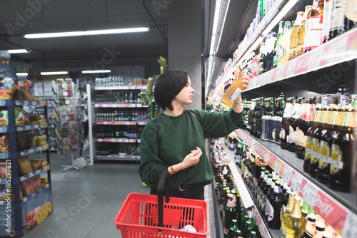 Poster de jardin Bar Beautiful young girl with a shopping cart, reading a label of an alcoholic beverage at a supermarket. Select a product in a supermarket.