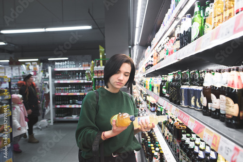 Poster de jardin Bar The girl looks at beer bottles in her hands. A girl chooses an alcoholic beverage at a supermarket. The choice of alcohol in the store