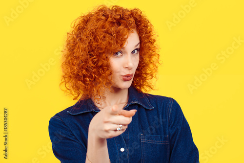 Obraz na plátně It's you! portrait of a beautiful woman redhead curly 80's retro style pointing at you camera happy isolated yellow background wall