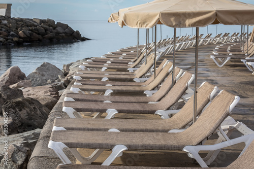 Row Of Sunbeds And Parasols At The Breakwater By The Beach