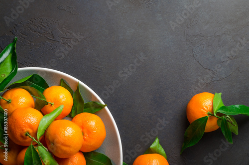 Fresh clementines on a gray plate on a dark black stone backgrou