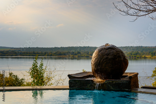 Peaceful round stone fountain overlooking the Zambezi river, Zambia, Africa Poster