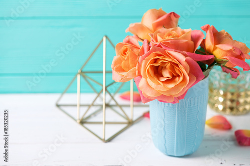 Photo  Bunch of fresh orange roses in blue cup on white wooden background against  turquoise  wall