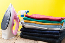 Iron And Stack Of Colored Clothes Yellow Background.