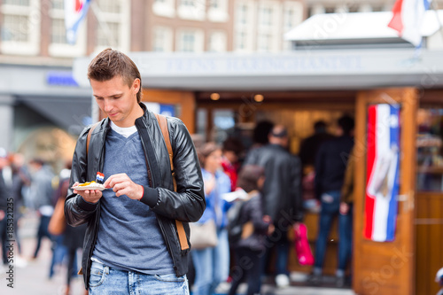 Happy caucasian tourist with fresh herring with onion and netherland flag in Amsterdam Canvas Print