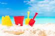 Kid's beach toys and straw hat on white sandy beach