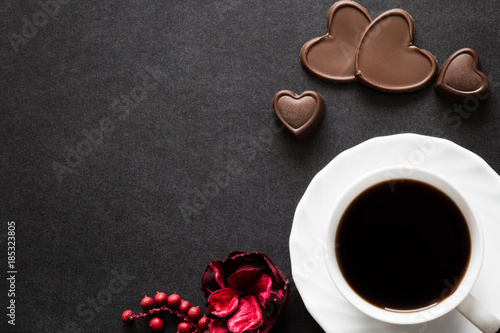 Cup of black coffee with chocolate hearts on the dark table. Enjoying a coffee and candies with beloved on the date. Empty place for a text.