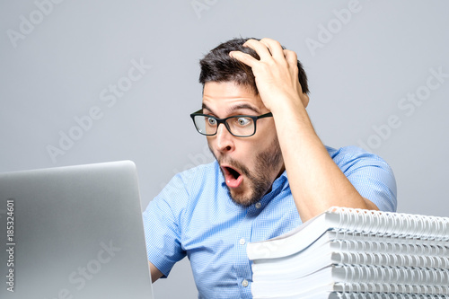 Fotomural Portrait of amazed man with laptop computer