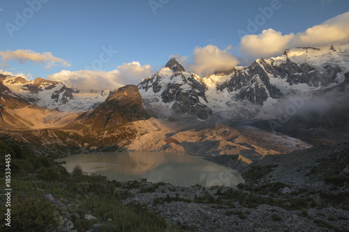 Aluminium Prints Salmon Summer views of the snowy mountains of the Caucasus. Formation and movement of clouds over mountains peaks.