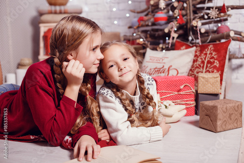 Girls sister friends hugging sitting at the Christmas tree, the concept of childhood, Christmas and New Year, on a light background