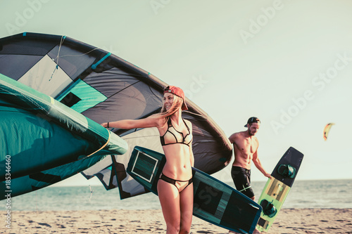 Pretty smiling Caucasian woman kitesurfer enjoying summertime on sandy beach with her boyfriend.
