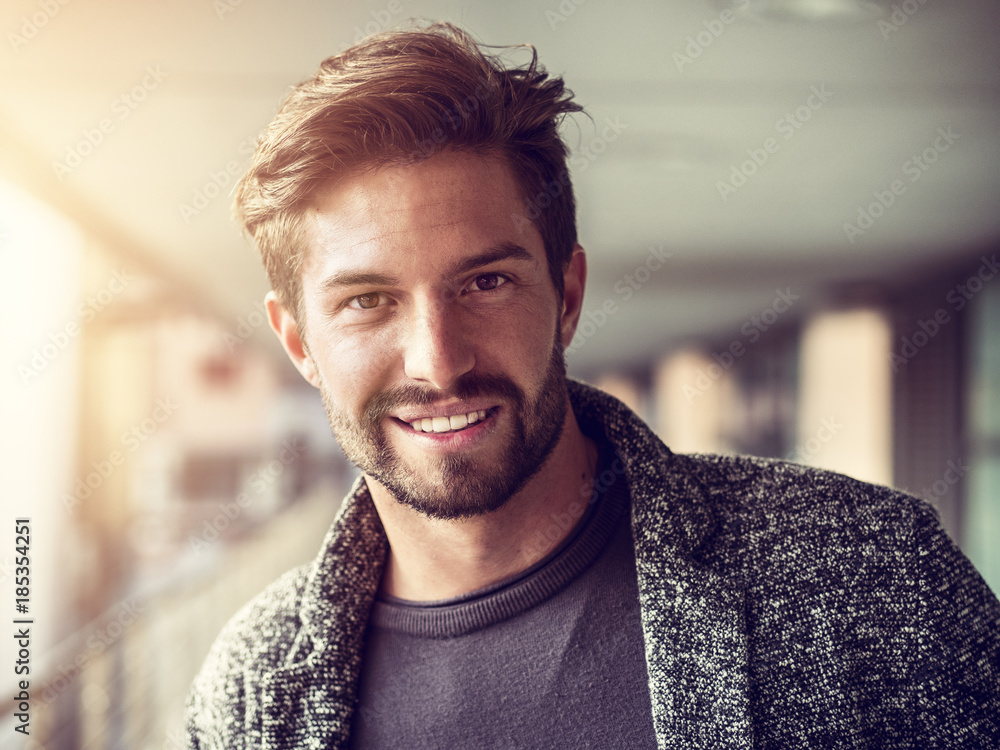 Fototapeta One handsome young man in urban setting in European city, standing, smiling and looking at camera