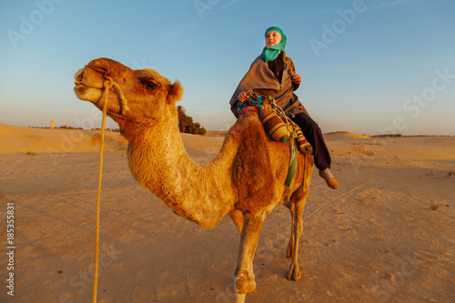 Woman  riding a camel in the Sahara desert.