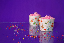 Two Cup Cake On The Blue Purple Background And Reflect On The Floor With Colorful Rounded Sugar Beads. Cupcake Is A Small Cake Baked In A Cup-shaped Container.