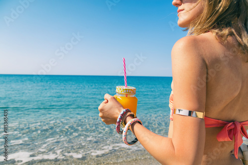 Poster Lieu connus d Asie Smiling woman holding orange juice in jar on the beach. Summer concept.