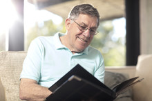 Smiling Senior Man Sitting On Couch Looking At Photo Album
