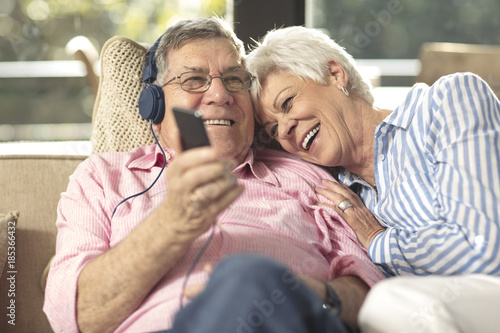 Happy senior couple with cell phone and headphones on couch at home