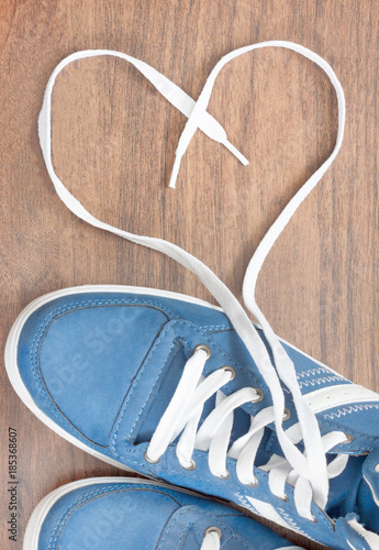 Photographie blue shoes with unbound lace in the shape of a heart on a wooden floor