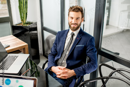 Принти на полотні Portrait of a handsome banker working with laptop sitting at the luxury office i