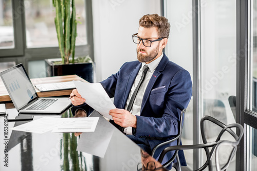 Fotografía Portrait of a handsome banker working with laptop sitting at the luxury office i