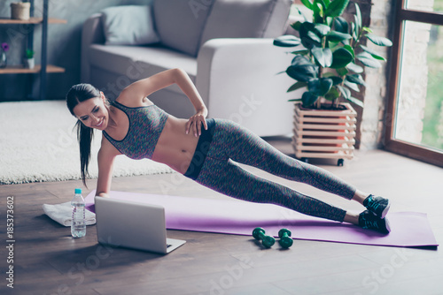 Fotografía Beautiful sporty cheerful woman is doing side plank exercise