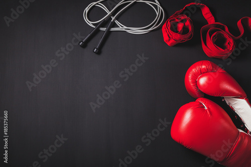 Fototapeta Professional red boxing gloves, wraps, and skipping rope on black background with copy space