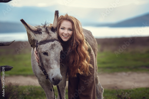 Deurstickers Ezel A girl with curly red hair in fashionable clothes in the style of Provence hugs a cute donkey