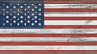 Old vintage American US flag over white wood