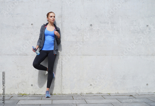 Fotografie, Obraz  Young, fit and sporty woman standing in front of concrete cement wall