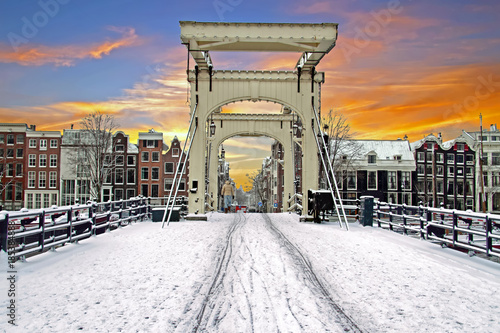 Photo  Snowy tiny bridge in Amsterdam the Netherlands in winter at sunset