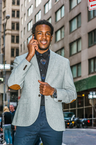 80de23af85 African American businessman traveling, working in New York. Young black  professional with beard walking through narrow, crowded high building  street, ...