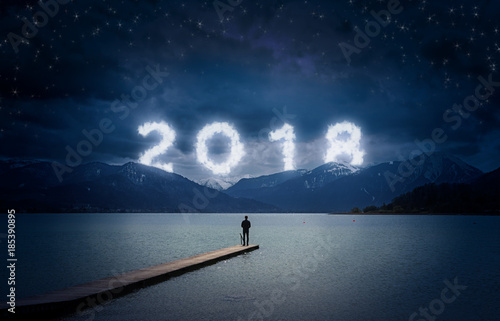 New year background, young man standing on a jetty in a lake and looking to the mountains under the dark sky with cloudy text 2018