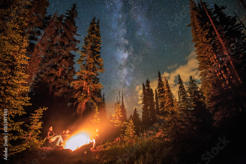 Photo Family of four sitting around a campfire under stars and the milky way
