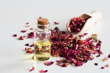 A Bottle Of Rose Essential Oil With Dried Rose Petals On White Background