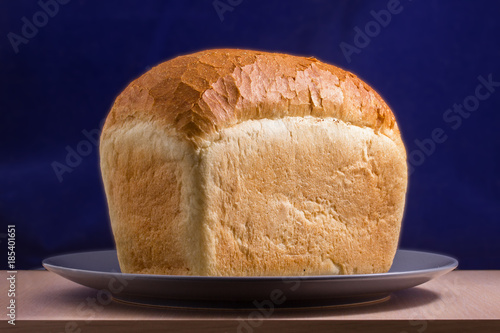 Slika na platnu large loaf of white bread on a plate on a table