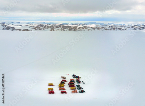 A group of snowmobiles is walking along the snowy plain Poster